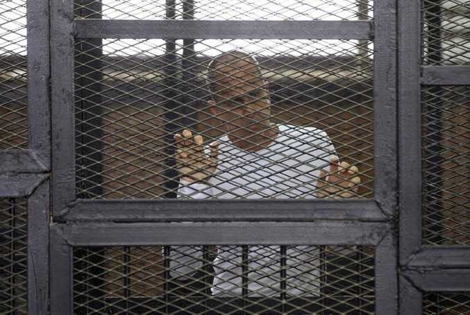 Al-Jazeera English correspondent Peter Greste appears in a defendant's cage in the police institute court house in Tura along with several other defendants during a trial on terror charges, in Cairo, Egypt, Tuesday, April 22, 2014. (AP Photo/Hamada Elrasam)