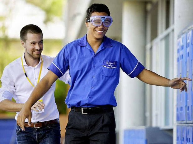 GROGGY: St Edmund's student Xavier Vela tries to walk a straight line while wearing beer goggles, assisted by Griffith University's Timo Dietrich.