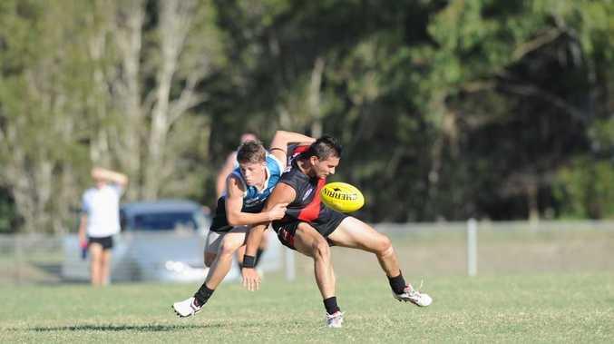 Aussie Rules - Bombers V. Bay Power. (L) Scott Burden puts a tackle on James Falkenberg.