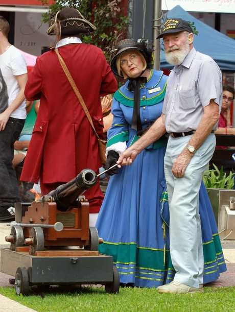 Lt Col Charles Mollison is honoured with the firing of the time cannon on the Town Hall Green on market day. He is assisted by Mary Heritage aka Carmel Murdoch. Photo: Robyne Cuerel / Fraser Coast Chronicle