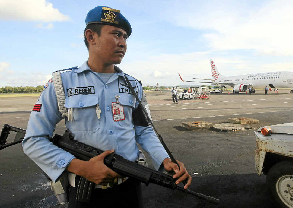 ON ALERT: An Indonesian Air Force member stands guard near a Virgin Australia airplane in Bali, Indonesia, yesterday.