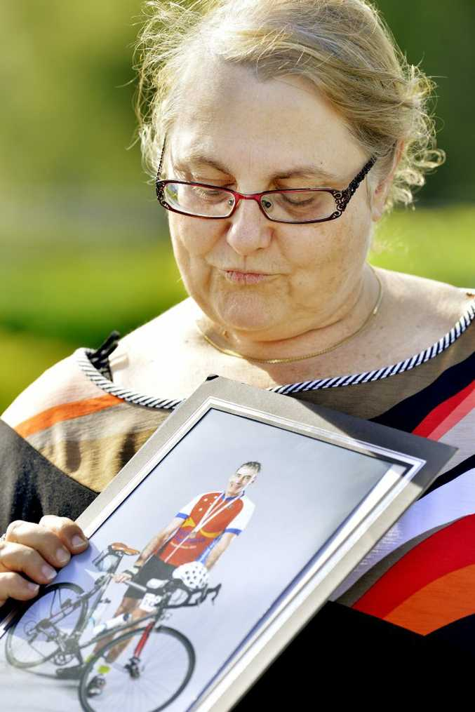 Sandy Vigar looks at a photograph of her late husband Dr Martin Pearson before addressing media outside Lowood Police Station. Ms Vigar is calling for any witnesses to her husband's suspected hit and run to come forward. Lowood cyclist Dr Martin Pearson was killed while cycling near Inglewood. Photo: Claudia Baxter / The Queensland Times