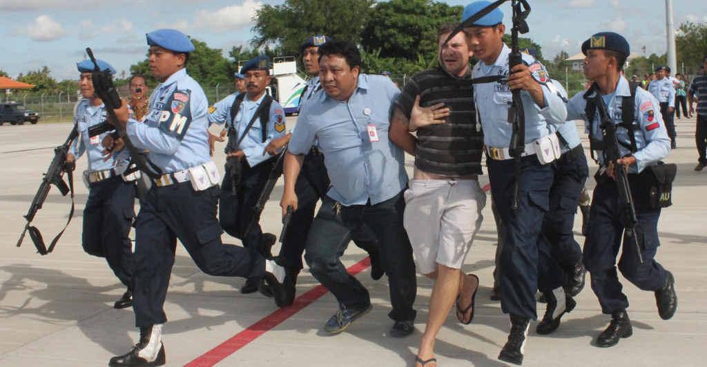WRONG DOOR: Indonesian Air Force soldiers rush Matt Lockley from a Virgin Australia plane at Ngurah Rai airport in Denpasar.