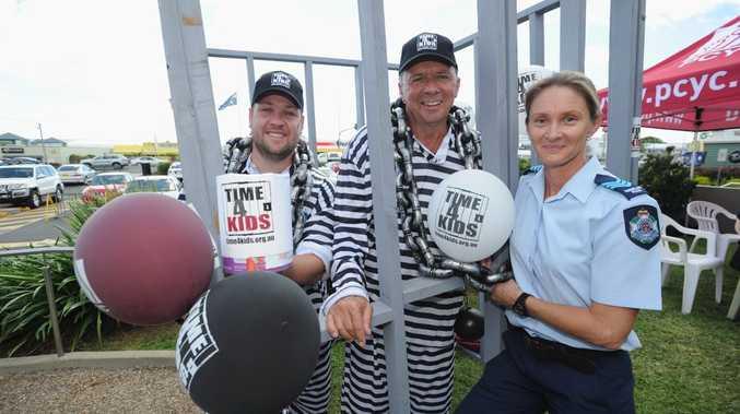 Ryan Bebbington of Mix FM and councillor Trevor McDonald get locked up outside Hervey Bay McDonald's by PCYC Hervey Bay branch manager Sergeant Tracey Meyers.