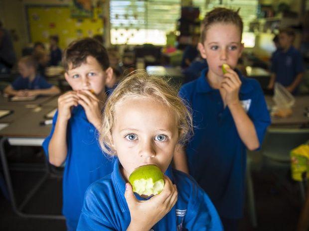 Year 2/3 Ambrose State School students Jacob Creed, 7, Julia Adams, 7, and Tomas Long, 8, enjoying their fruit break.