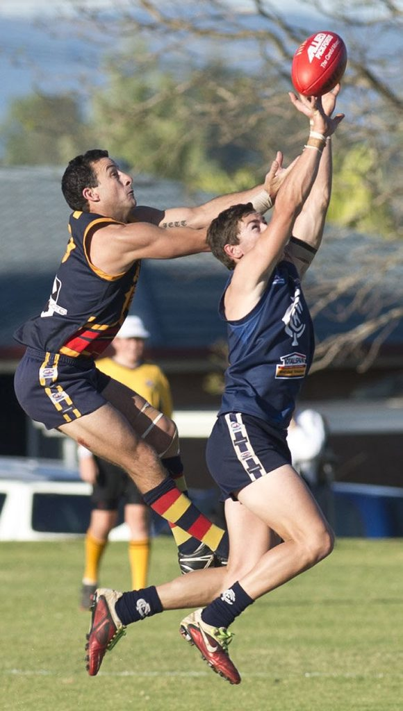 University's Heath Gniel leaps above Coolaroo's Jarron Miller in last year's AFL Darling Downs grand final.