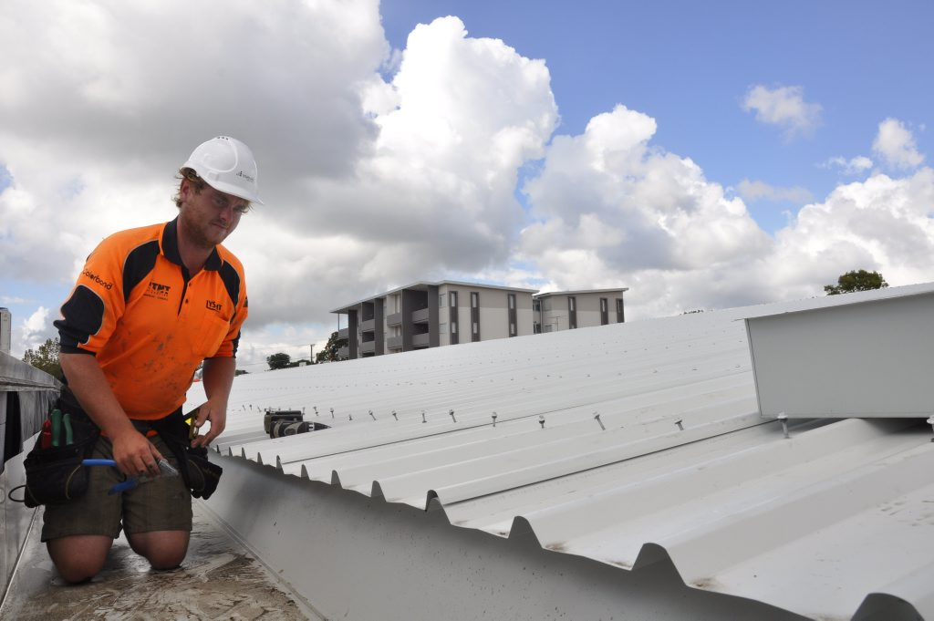 TNT Roofing supervisor John Ford secures sheets of replacement roofing to a Hooper Centre building.