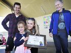 BRAVE GIRL: Dr David Meldrum (right) presents Charlotte Fox with her bravery award, as Brooke and Aaron Fox look on.