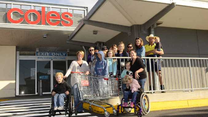 WORTH THE WAIT: Patricia Verran and her son Bailey (left) and friends Jess White and others who supported the call in getting a new special shopping trolley in Coles Yamba. Photo Debrah Novak