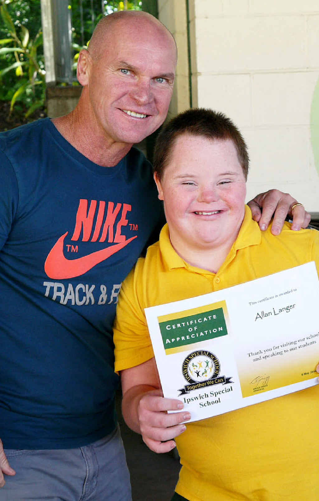 MEMORABLE DAY: Ipswich Special School student Rhys Bramich presents league legend Allan Langer with a certificate.
