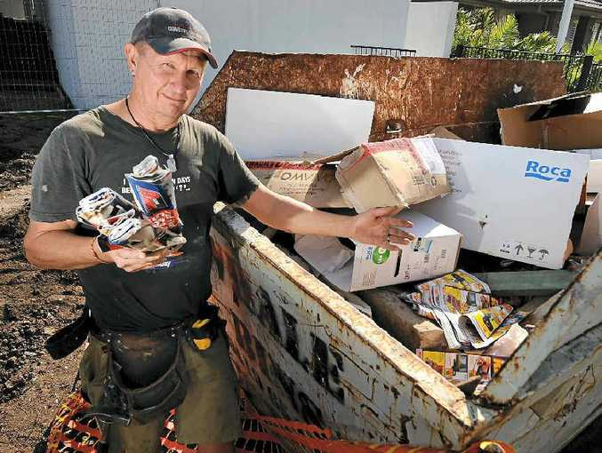 MONEY WASTE: Planet Homes employee Raoul Resser with one of the skips filled with other people's junk, which his boss, Jason Bowker, has to pay to dump.