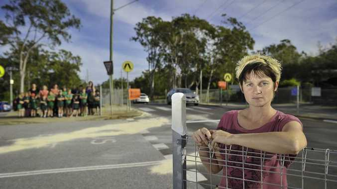 TOO CLOSE: Teneille Wode in front of the remnants of the most recent crash at the pedestrian crossing at Clinton State School.