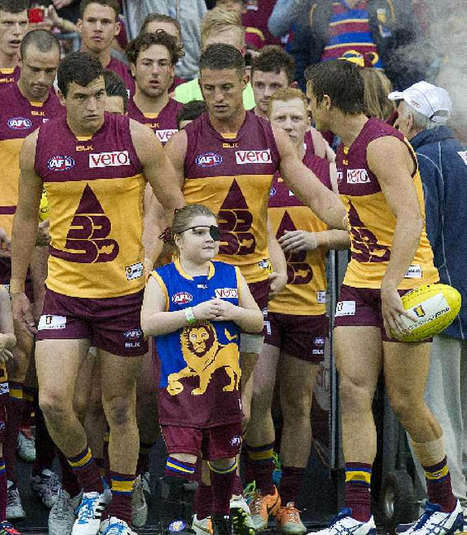 Tobi Wilkinson (centre) prepares to run on to the field with the Brisbane Lions.