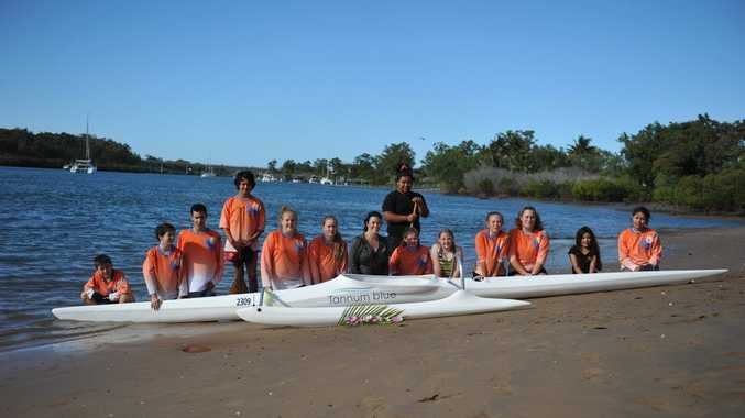 Kym Purcell from Tannum Blue with the Canoe Point Outriggers junior team and the new V1 Canoe which was donated.