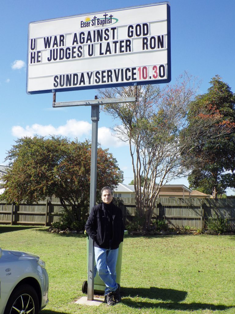 Anti-school chaplaincy campaigner Ron Williams stands under the Eiser St Baptist Church sign which seems to criticise his High Court challenge.