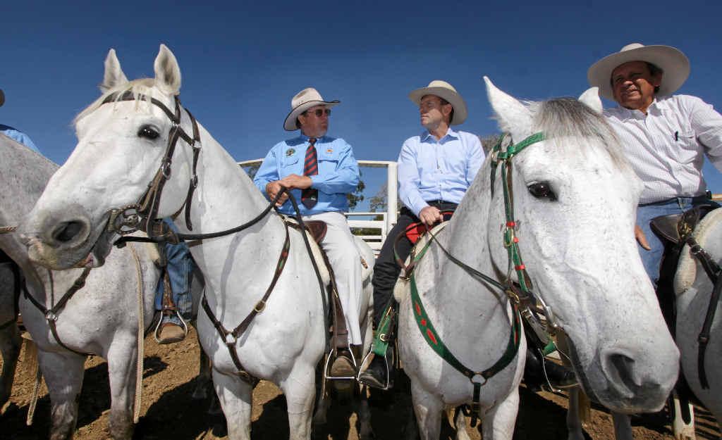 Opposition Leader Tony Abbott on horseback flanked by Cattlemen Graeme Acton and Cameron McIntyre at Acton's property Paradise Lagoons outside Rockhampton.