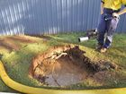 A large hole was left in the footpath after a water main burst in Agnes St, Centenary Heights. Photo: Stuart Cumming / The Chronicle
