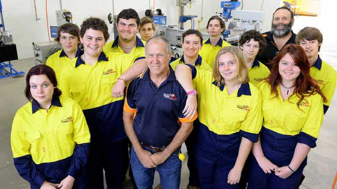 JOB READY: Ipswich State High students and trainer Neville Jesse (front) applaud the opening of the new trade training centre.