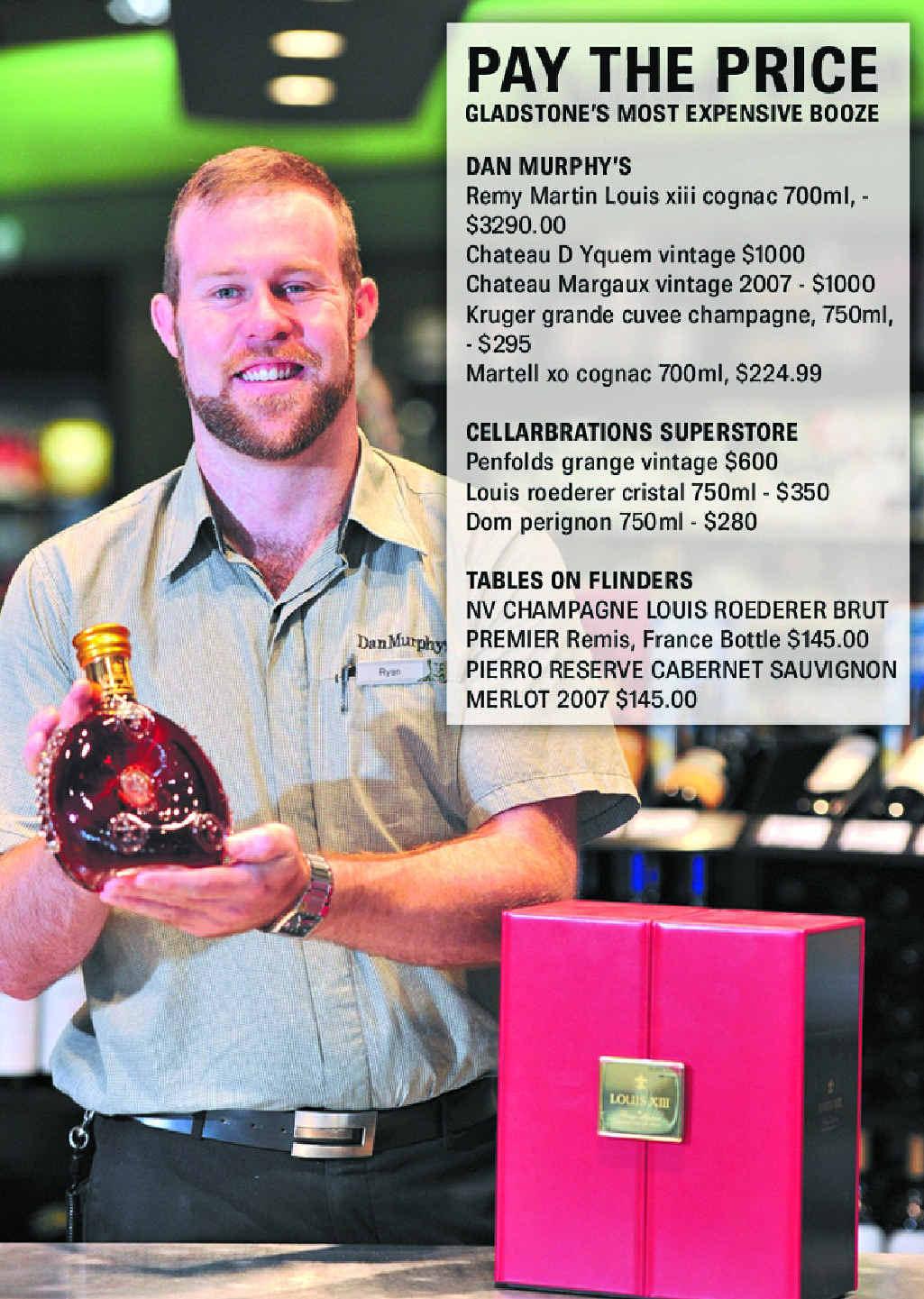 Dan Murphy's Gladstone customer experience manager Ryan Lobegeier is holding a $3000 bottle of Cognac.