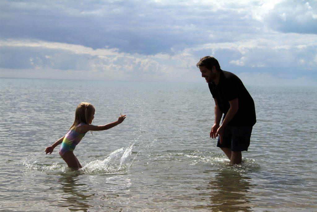 Sydney tourists Maya Mitchell, 5, and her dad Derek Mitchell are unfazed by a croc sighting at Urangan beach.