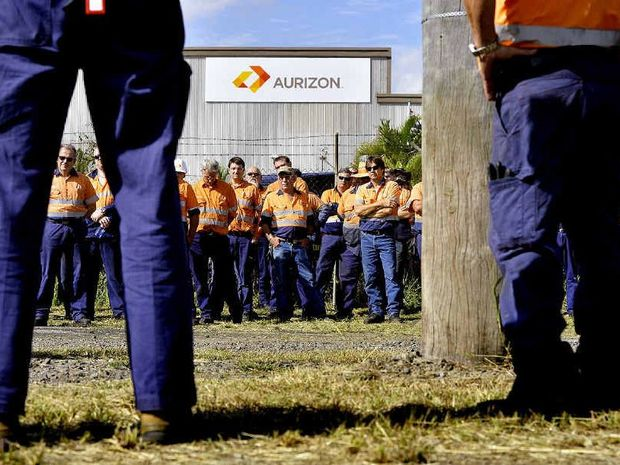 GRIM: Aurizon workers at the Redbank workshops listen to union delegates at a meeting yesterday. Aurizon will shed 450 workers by June 2015.