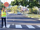 SAFE JOURNEY: Geoff Watson has been a crossing supervisor – or lollipop man – at Ipswich Central State School for 30 years.