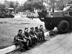 South Vietnamese officers sit dejectedly on a curb outside the Presidential Palace shortly after North Vietnamese troops captured the Palace in Saigon on April 30, 1975.