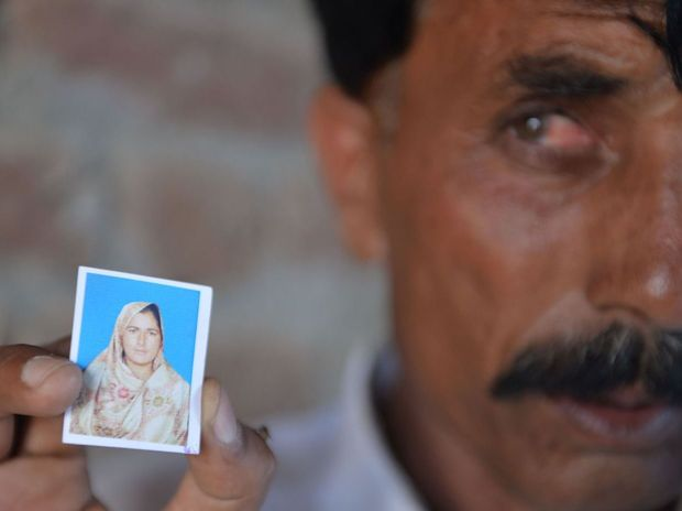 Pakistani resident Mohammad Iqbal poses for a photograph as he holds up an image of his wife Farzana Parveen, who was beaten to death with bricks by her father and other family members for marrying a man of her own choice.