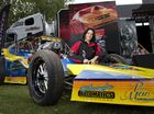 Jennifer Harrison of the Australian National Drag Racing Association with a drag racing car owned and raced by Toowoomba's Rodney Hansen at a display to promote the sport in Queens Park.