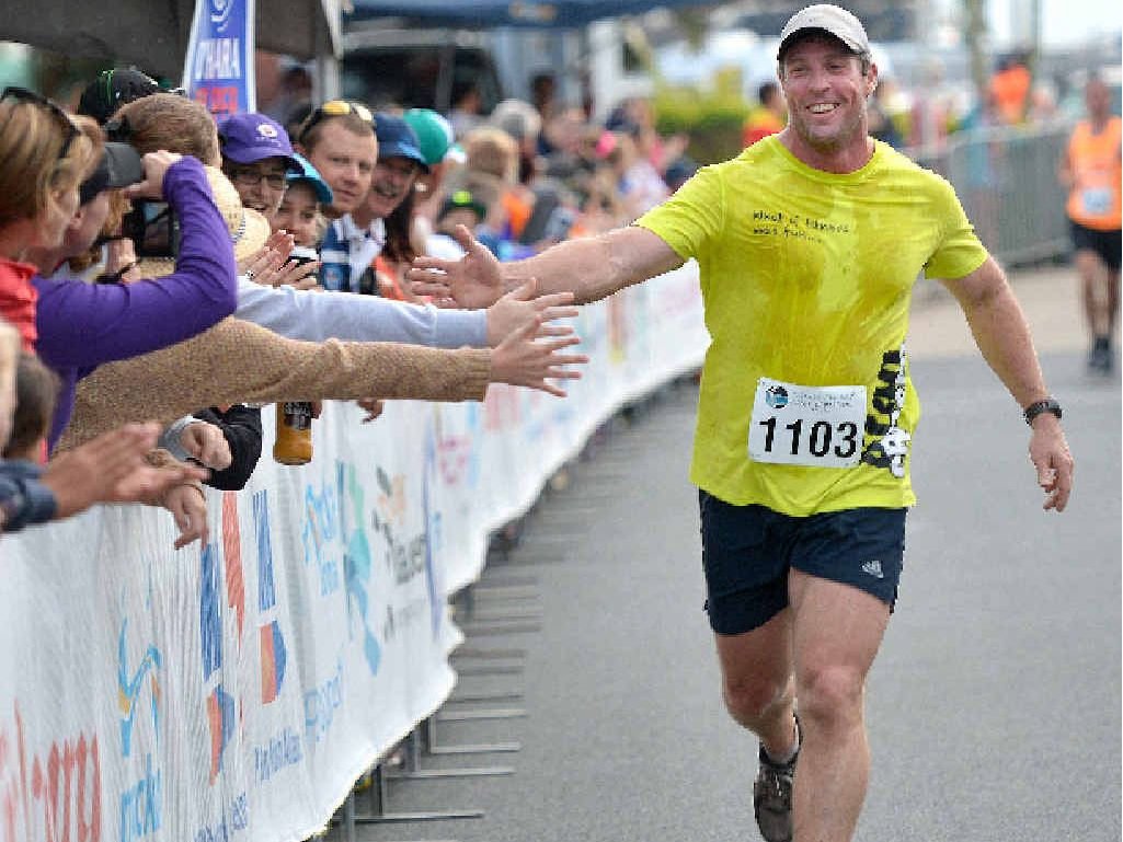 Wayne Davis is cheered on by spectators as he reaches the finish line of the Dalrymple Bay Coal Terminal 8km run, which was part of yesterday's BMA Mackay Marina Run.