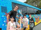 COLOURFUL: Jack Quinn, on the ladder, and Hatsie and Brydie Brakels with their mum Kendall Perkins, who painted the bus for the event.