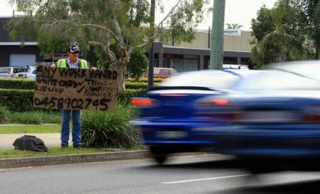 Hervey Bay man Graham Smyth, 54, stands beside the road with a sign in the hope of being offered work.