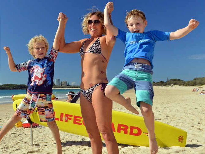 THUMBS UP: Elijah Sole,6, Danna Morrissey, and Isaac Sole,8, make the most of the beautiful weather at Mooloolaba Beach.