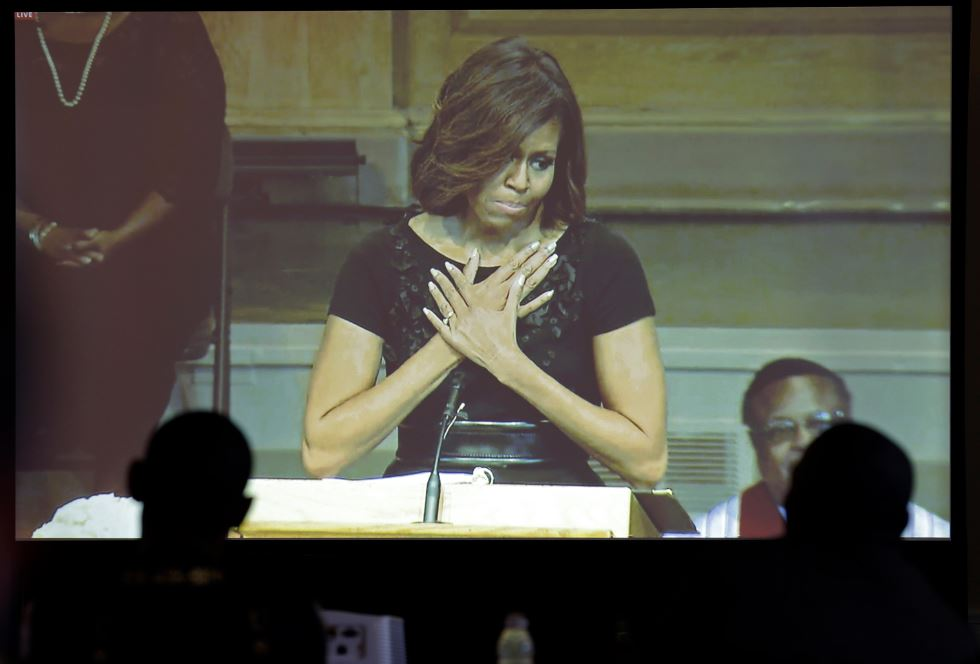 Media members watch on a screen as First lady Michelle Obama speaks during a memorial service for poet and author Maya Angelou at Wait Chapel. at Wake Forest University in Winston-Salem, N.C., Saturday, June 7, 2014.