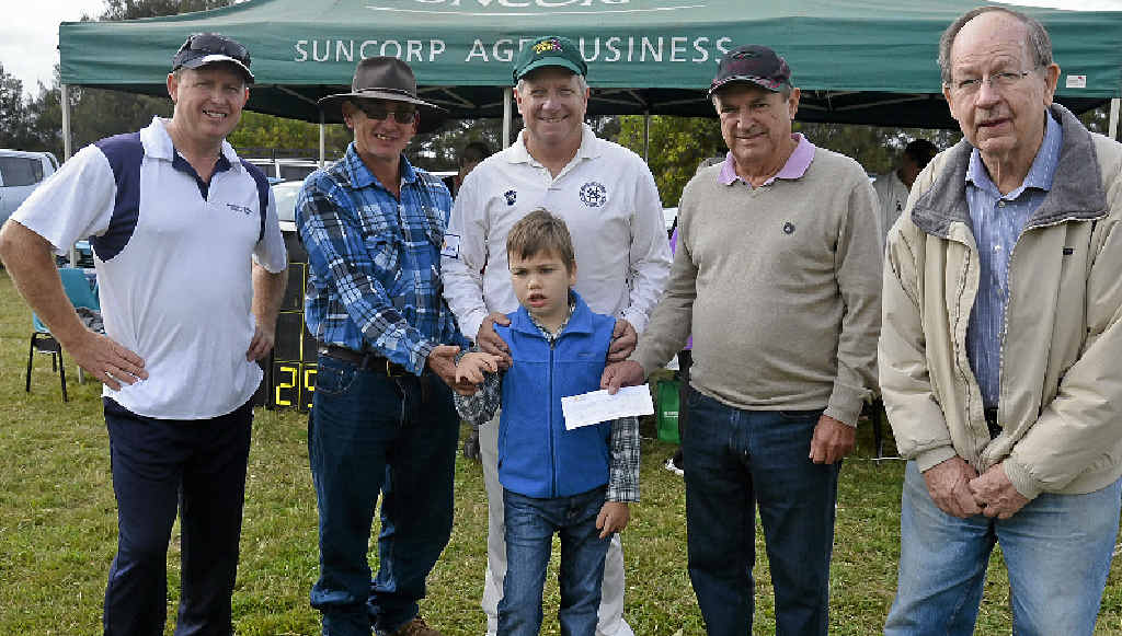 FUNDS FOR FAN: Kevin Bourke, Phil Bowles, former Australian keeper Ian Healy, Australian Cricket Society member Robin Farrell, Nick Szkutko and (front) Angus Bowles, after the society presented a $500 cheque to the Maryvale Cricket Club fundraising effort to help Angus.