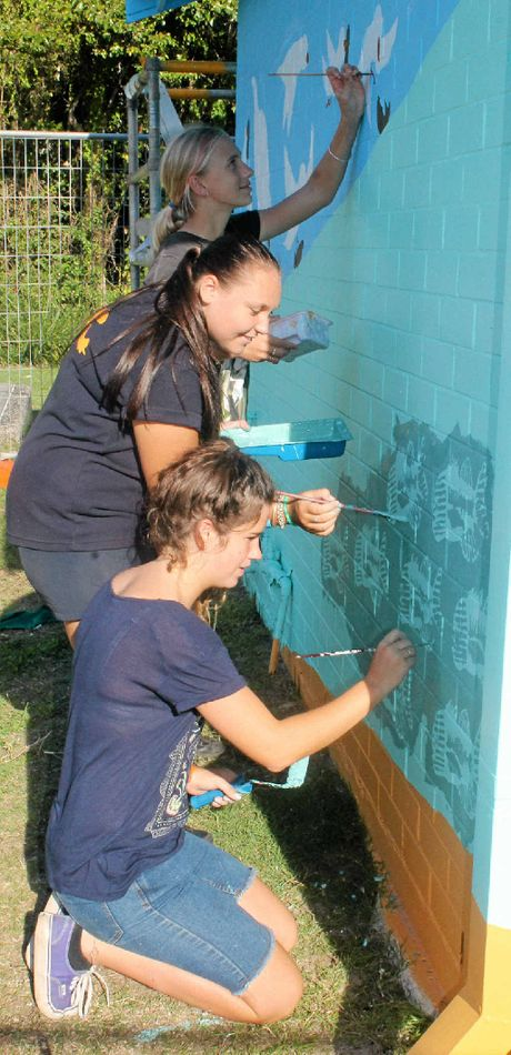 SMELLY CANVAS: Southern Cross School K-12 students (from back to front) Shianna Wyatt-Peters, Kelsie Wareham and Jasmin Mowbray at work painting a mural on the sewage pump station near Chickiba Lake, East Ballina. Pictured above left is the finished work.