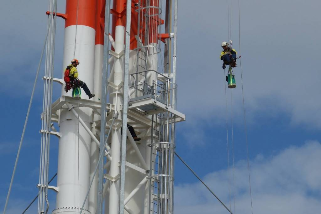 Painters have been abseiling down a 97m tall tower doing touch-up work on the QCLNG project on Curtis Island.