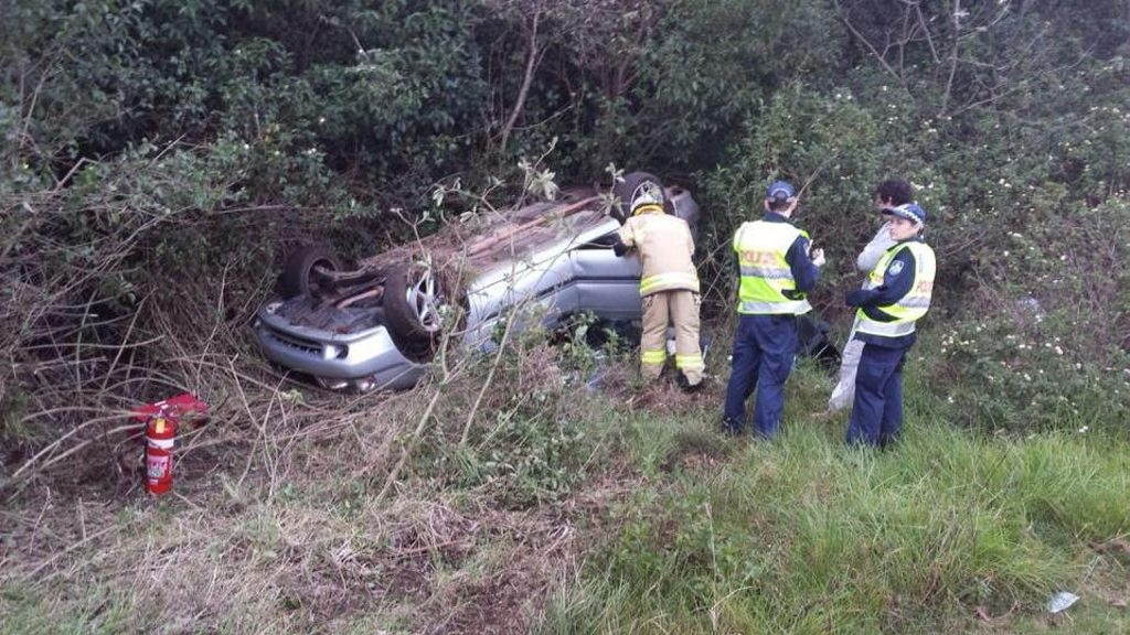 Emergency services inspect a vehicle which rolled down an embankment beside the New England Hwy at Blue Mountain Heights.