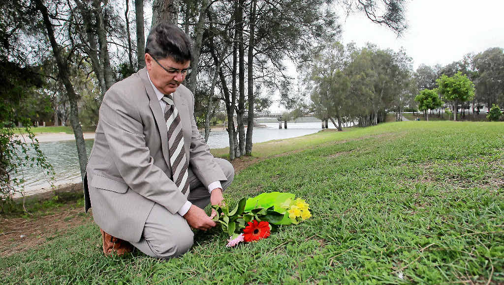 LIVING IN HOPE: Dwayne Cunningham places flowers in the park at Picnic Point where he believes his mother Deirdre might have been on the night she disappeared.