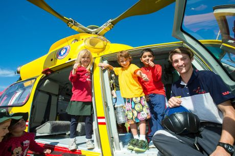 Westpac crewman Callum Fry shows Woolgoolga Public School students Mianna Wood, Oscar Reynolds and Sahib Singh through the helicopter on Thursday.