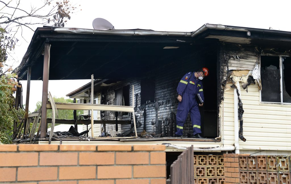 An investigator from the Queensland Fire and Rescue Service inspects a North Ipswich home that was engulfed by flames in the early hours of Saturday. Photo: Rob Williams / The Queensland Times