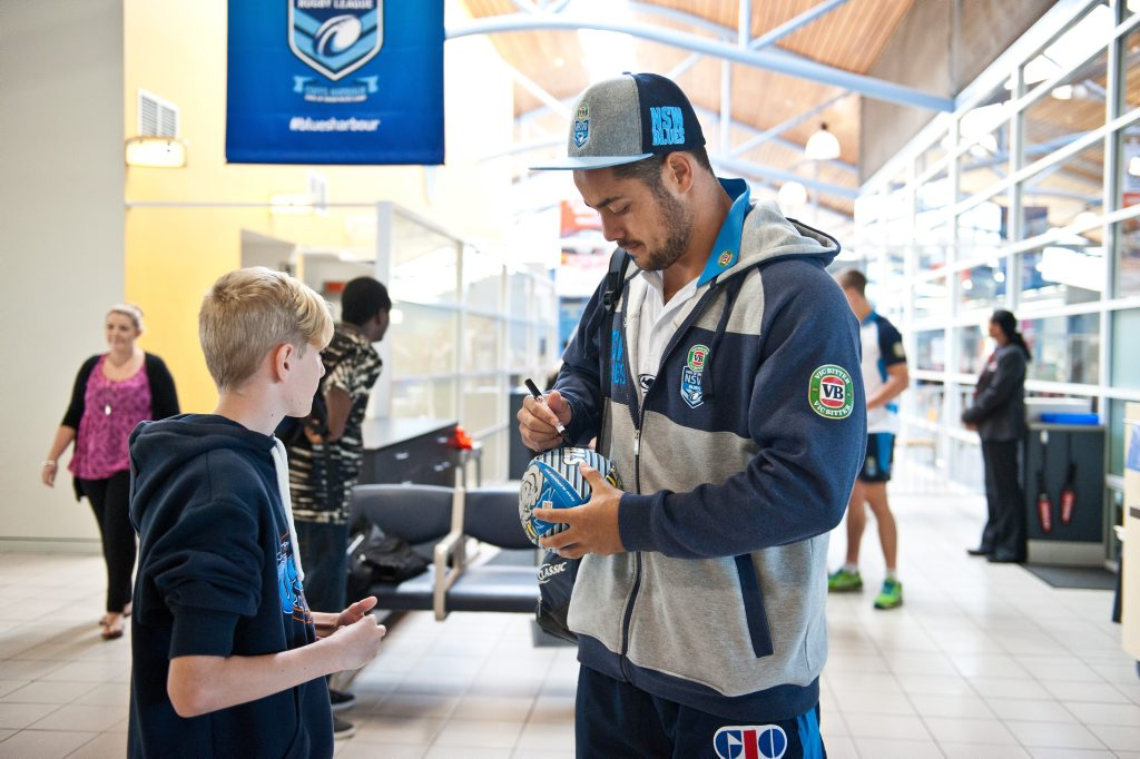 Jarryd Hayne signs a ball for Bryce Sully as the Blues fly out of Coffs Harbour.