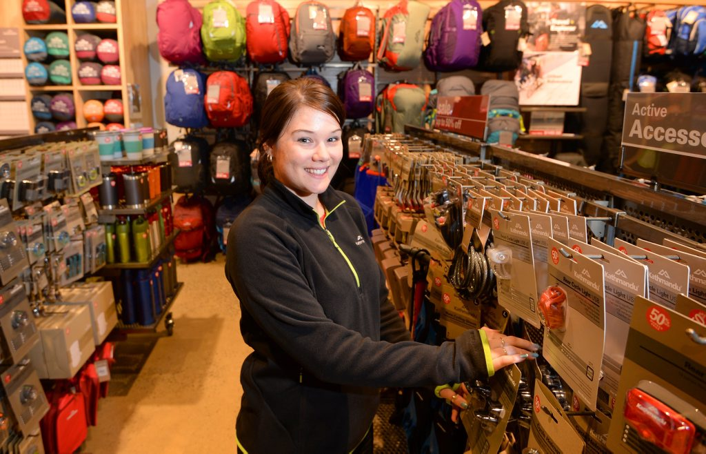 Kathmandu store manager Kylie Stoch arranges stock in the new store at Stockland Rockhampton. Photo: Chris Ison / The Morning Bulletin