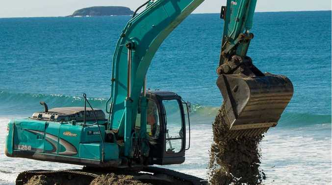 BETTER BEACH: An excavator distributes the growing sand levels on Park Beach as siltation is pumped from the harbour.