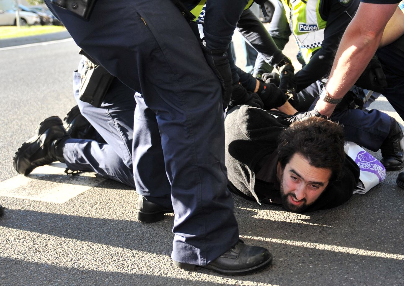 POLICE detain a protester shortly after Foreign Minister Julie Bishop left Melbourne University after speaking at the opening of C20 in Melbourne, Friday, June 20, 2014. Students were protesting outside the opening of the C20 summit, which stands for Community 20, one of a number of lead up summits to the G20 in Brisbane later this year.
