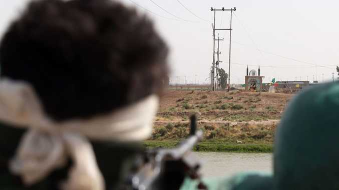 An Iraqi Turkmen fighter looks at an icon of the seventh century Imam Ali bin Abi Talib, Islam's fourth caliph and cousin and son-in-law of Prophet Mohammed, located in no-mans land between the Turkmen fighters and jihadist Islamic State of Iraq and the Levant (ISIL) fighters in the disctrict of Taaza, 25 km south of Kirkuk, on June 21, 2014.