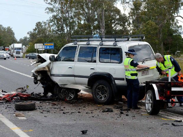 HORROR: Police investigators look over the scene of a head-on collision on the Bruce Hwy on Sunday. An 83-year-old driver of a Hyundai i20 died instantly.
