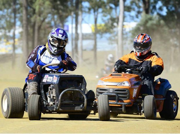GOING HARD: Brisbane Mower Sport club president Rob Kirkwood (left) throws his machine into a corner ahead of another competitor at Willowbank.