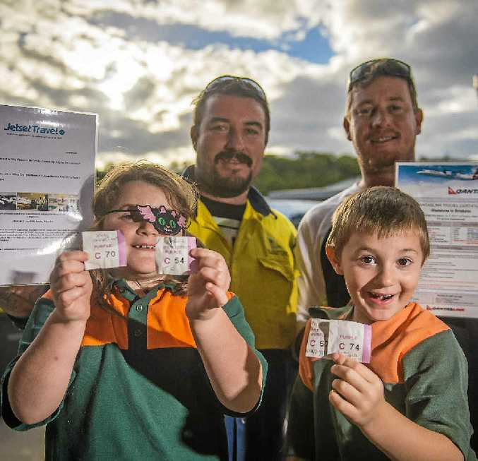 WINNERS: Tobi, Paul, and James Wilkinson and Jason Keysworth with raffle prizes and winning tickets for the raffle drawn in support of the Wilkinson family at the Gladstone council depot.