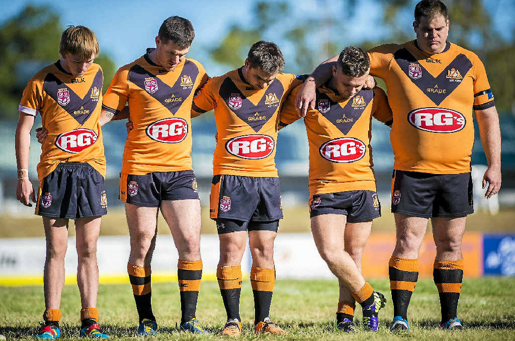 SAD MOMENT: Ashley Cochrane (second from right) observing a minute's silence at the Wallabys versus Seagulls match at Marley Brown Oval.